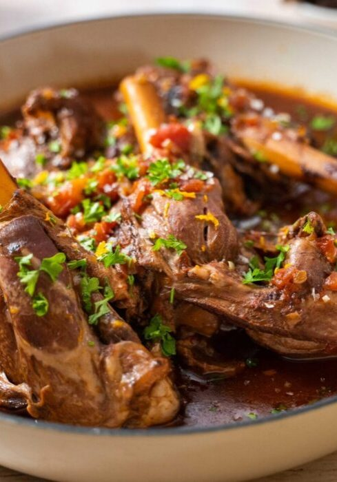 Meat with bones in a brown stew in white casserole dish, green herbs and red food scattered over. Slices of bread on wooden board, pots of salt pepper in the back.