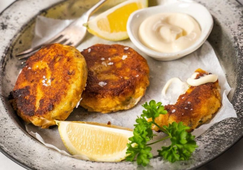 Fish cakes on a plate with lemon wedges, parsley and tartar sauce on a plate