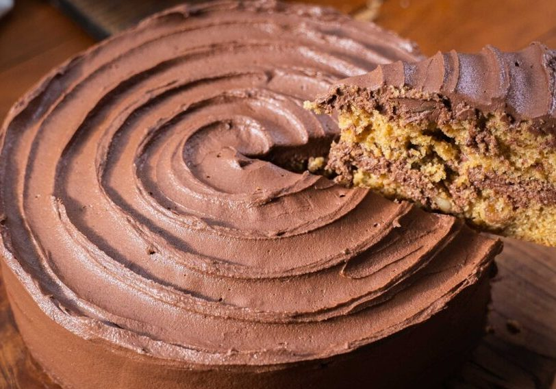 Close-up of a large round chocolate cream cake on a wooden board with a slice lifted up to reveal layers.