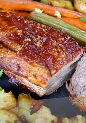 Cooked pork sliced surrounded by potatoes and vegetables on black slate.