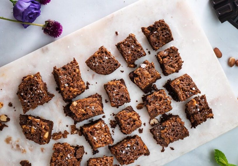 Chocolate brownie pieces on a white marble board, purple flowers, green herb, chocolate and nuts around them.