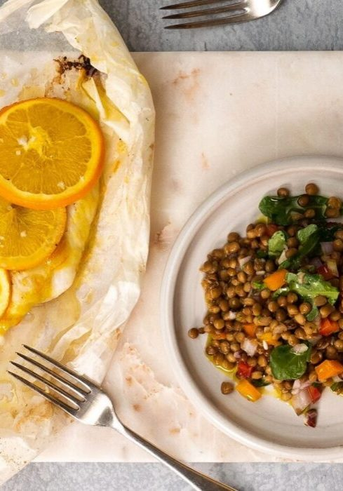 White fish topped with 3 orange slices on a baking paper with a fork, a plate of colourful lentil salad on the right side of it.