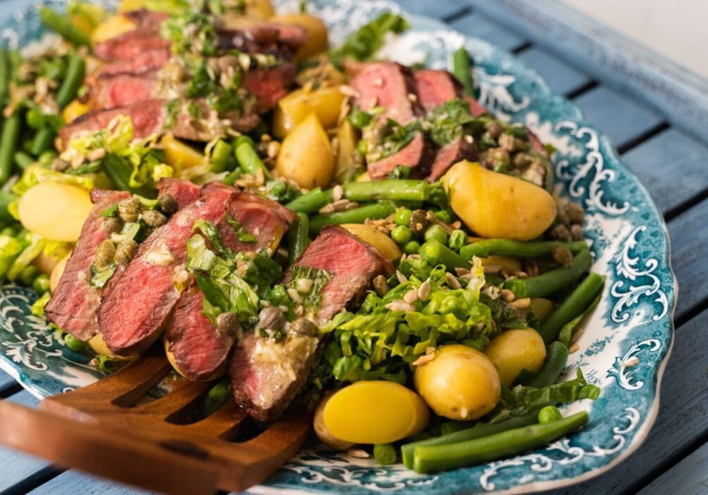 A blue platter of potato, meat and green salad with a wooden salad server on a large blue tray.
