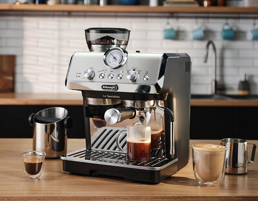 De'Longhi La Specialista Arte coffee machine on a wooden kitchen bench with a selection of coffees and accessories around